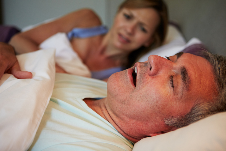man snoring in bed with wife who is awake